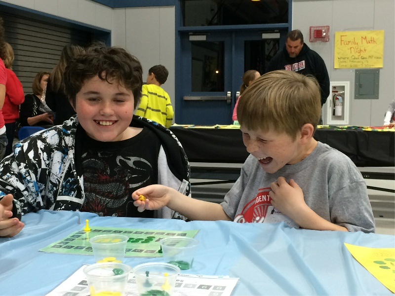 Two kids laughing while doing a Family Math Night activity